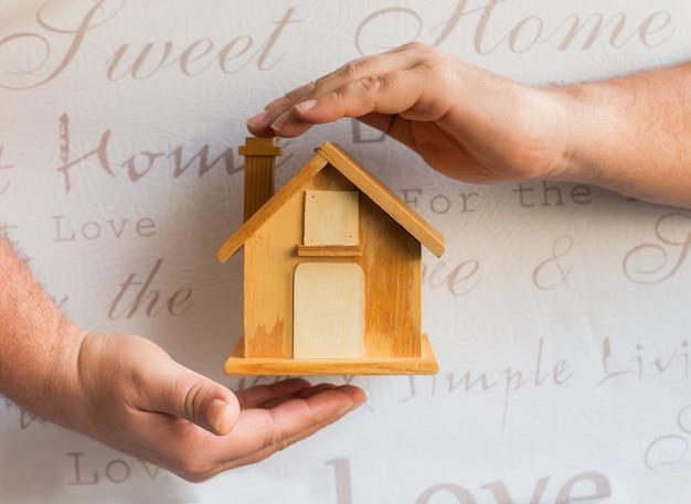 Masculinas mãos em torno de uma pequena casa de madeira