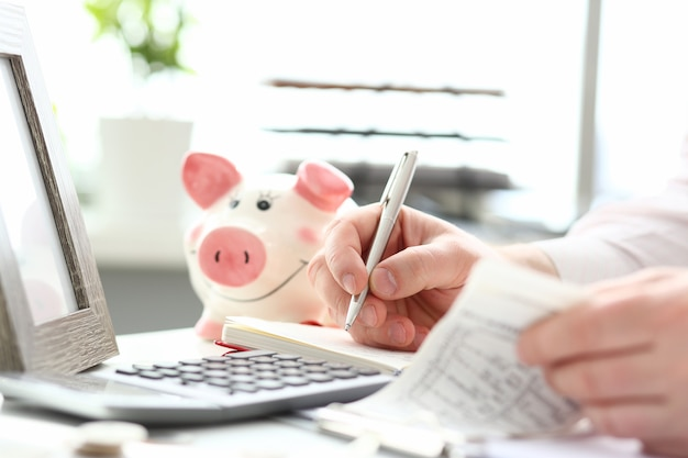 Masculinas mãos fazendo anotações com caneta prata sobre orçamento familiar
