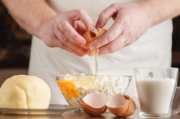 Masculinas mãos quebrando ovos em uma tigela; fechar-se