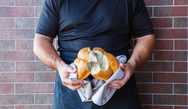 Masculinas mãos quebrando pão fresco