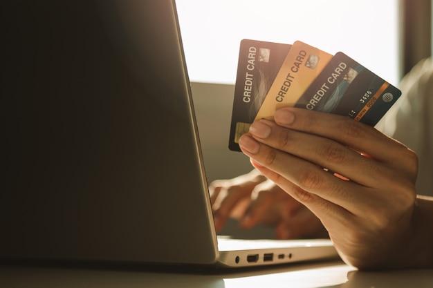Masculinas mãos segurando um cartão de crédito e usando o laptop na mesa de trabalho