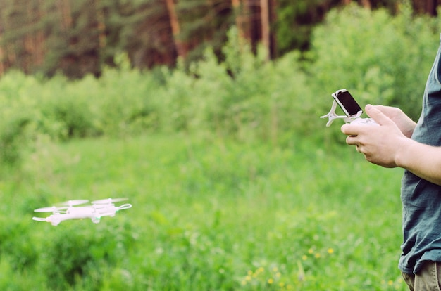 Masculinas mãos segurando um controle remoto com um smartphone de um quadrocopter no fundo de grama e zangão. o conceito de tecnologia moderna, voando.