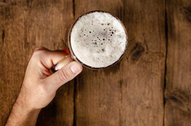 Masculinas mãos segurando um copo cheio de cerveja loira.