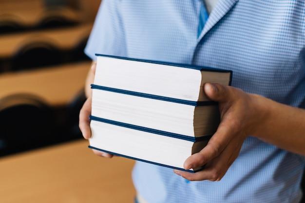 Masculinas mãos segurando uma pilha de livros.