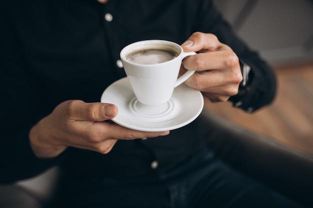 Masculinas mãos segurando uma xícara de café