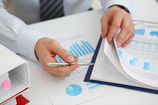 Masculinas mãos segurar documentos com estatística financeira