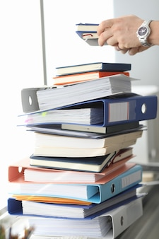 Masculinas mãos trabalhando em pilhas de arquivos em papel