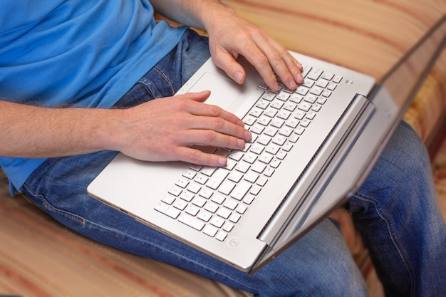 Masculinas mãos trabalhando em um laptop enquanto está sentado no sofá
