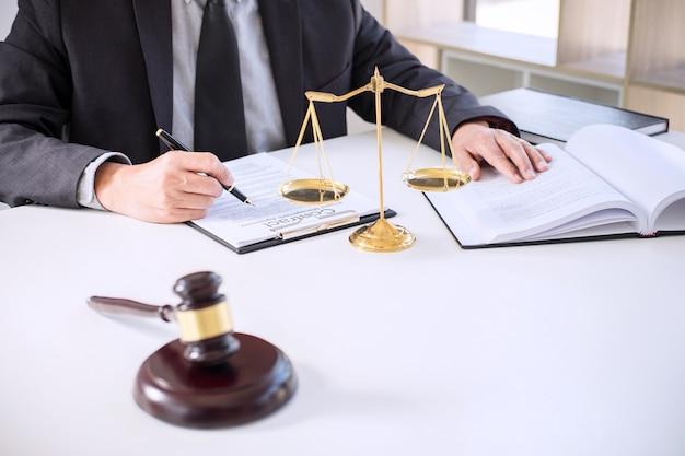 Masculino advogado ou juiz trabalhando com livros de direito, martelo, relatar o caso na tabela