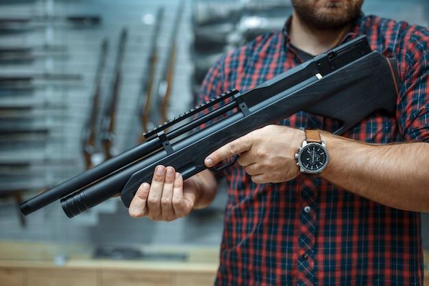 Masculino com rifle pneumático em vitrine de loja de armas