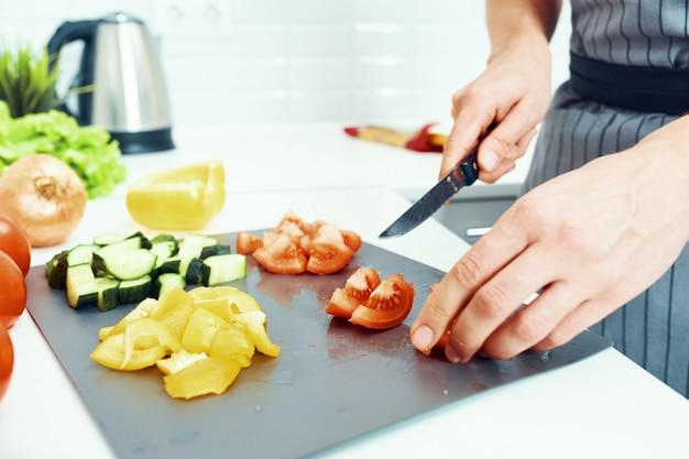 Masculino cozinheiro cozinha na cozinha, comida caseira saudável