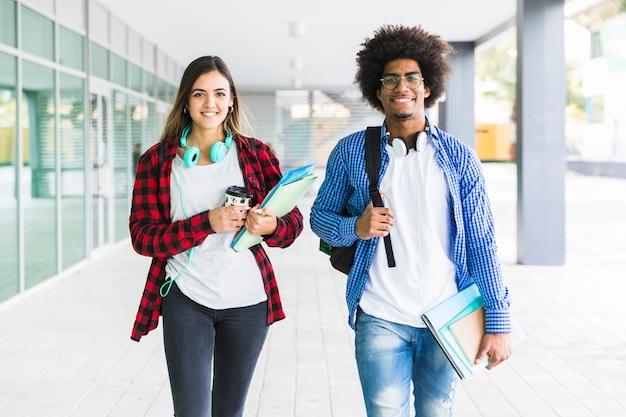 Masculino e feminino estudante segurando livros na mão, andando no corredor da faculdade