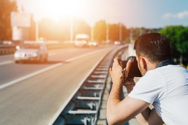 Masculino fotógrafo tirando fotos da estrada da cidade
