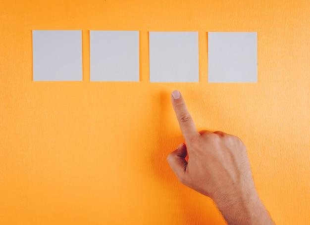 Masculino mão apontando para nota papéis na laranja