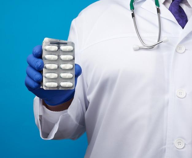 Masculino mão com luvas estéreis azuis detém uma pilha de comprimidos em blister
