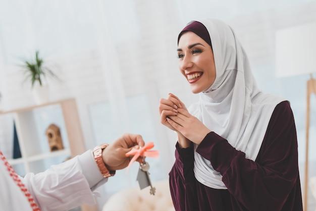 Masculino mão dá chaves de casa feliz senhora em hijab.