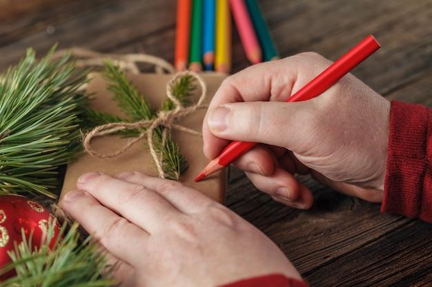 Masculino mão embrulhado presente de natal no jornal na mesa de madeira escura, vista superior