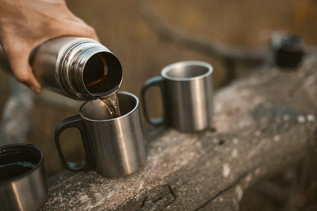 Masculino mão está derramando uma bebida quente de uma garrafa térmica em copos de metal camping em pé em uma árvore caída