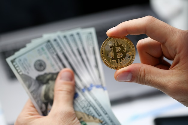Masculino mão segura bitcoin e moeda de dólar