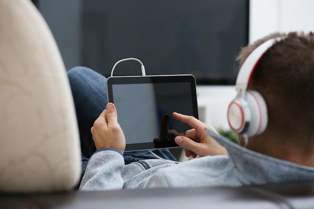 Masculino mão segura tablet em ambiente doméstico enquanto