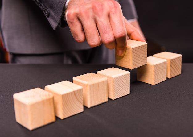 Masculino mão segura um cubo de madeira na mão.