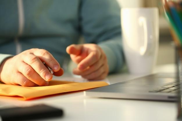 Masculino mão segurando a caneta prata. preencha o endereço no envelope amarelo da correspondência para o conceito de contratação de aplicativos