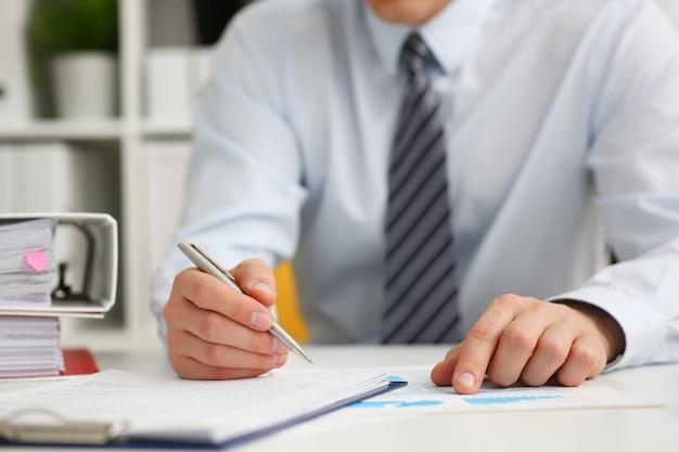 Masculino mão segurando a caneta prata pronta para escrever