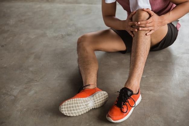 Masculino mão segurando a lesão no joelho
