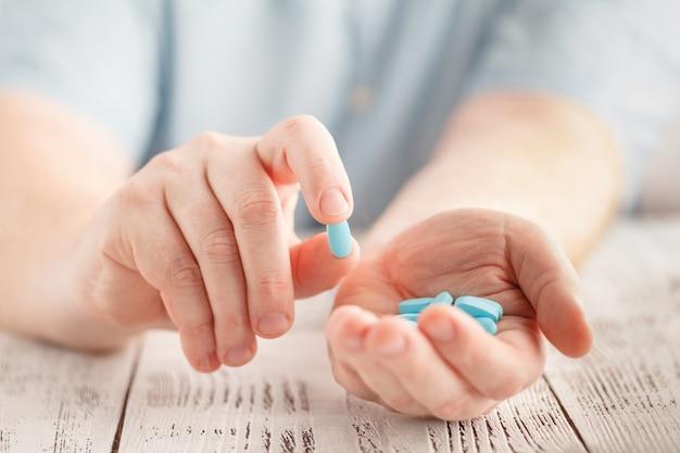 Masculino mão segurando comprimidos azuis na palma da mão