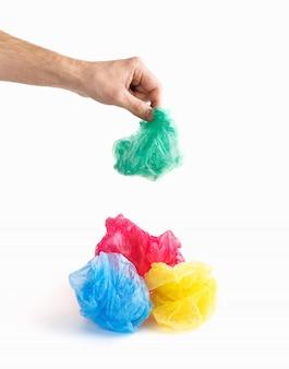 Masculino mão segurando o polietileno verde sobre sacos de plástico enrugados multicoloridos juntos isolado no fundo branco