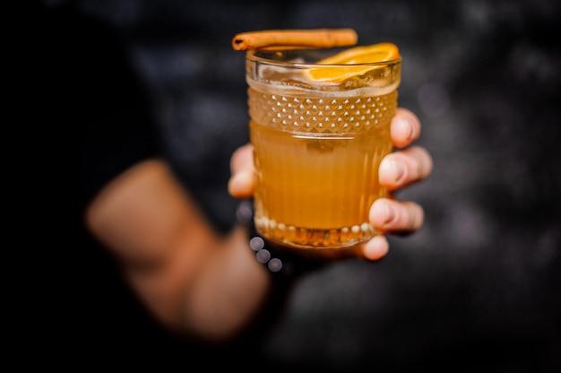 Masculino mão segurando um copo de bebida alcoólica laranja fresca