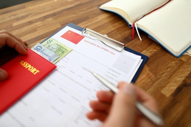 Masculino mão segure caneta prata com passaporte