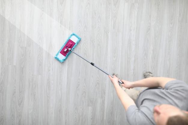 Masculino mão segure esfregão plástico e lave o chão sujo closeup
