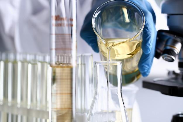 Masculino mão segure o líquido amarelo no tubo de ensaio.