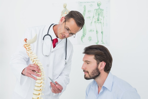 Masculino médico explicando a espinha a um paciente