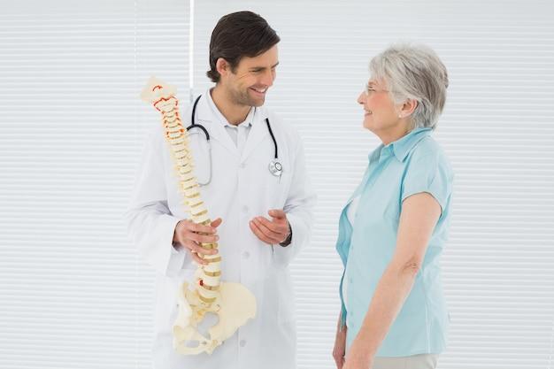Masculino médico explicando a espinha para um paciente sênior