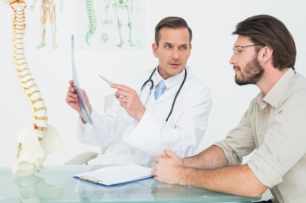Masculino médico explicando xray da coluna para o paciente