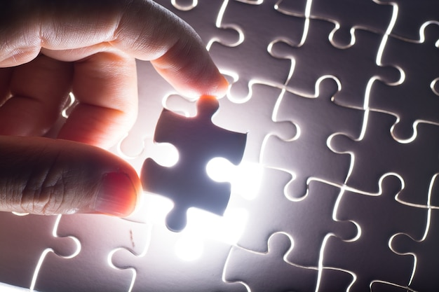 Masculino ou homem mão e dedo colocar piece of jigsaw in place