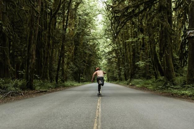 Masculino patinando em uma estrada vazia no meio da floresta