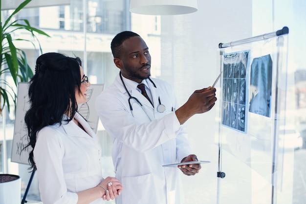 Masculinos africanos e caucasianos médicos femininos discutindo os resultados da ressonância magnética do paciente no hospital. médicos masculinos e femininos em jalecos brancos com estetoscópios. conceito de medicina e saúde.