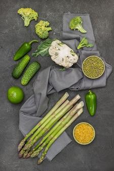 Mash e bulgur em tigelas. espargos, meia couve-flor, brócolis em guardanapo cinza. pepinos e pimentões na mesa. fundo preto. postura plana