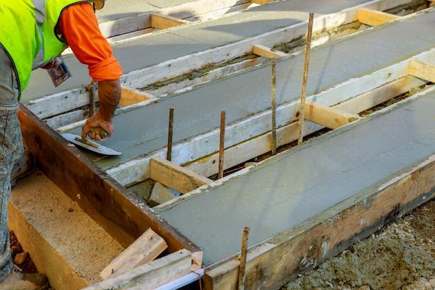 Mason, construindo um cimento de revestimento de mesa no trabalho de chão. derramando pavimento de concreto