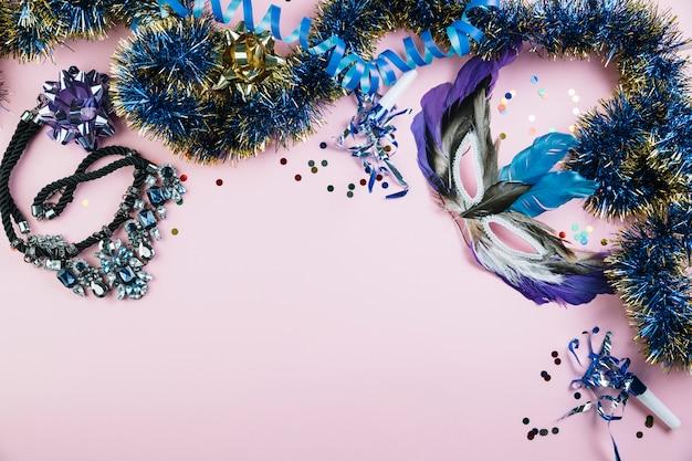 Masquerade máscara de penas de carnaval com material de decoração brilhante no fundo rosa