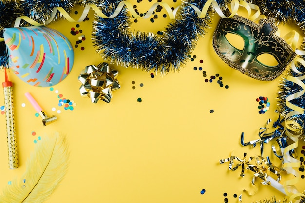 Masquerade máscara de penas de carnaval com material de decoração de festa e chapéu de festa sobre fundo amarelo