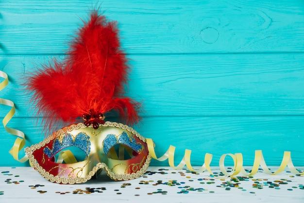 Masquerade máscara de penas de carnaval com serpentina amarela e confetes
