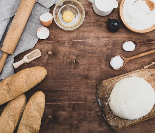 Massa amassada e ingredientes para fazer pão