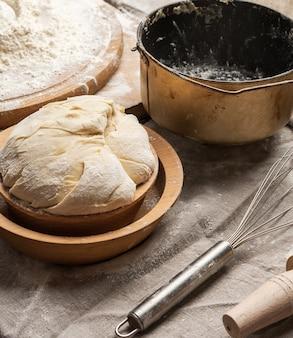 Massa amassada feita de farinha de trigo branca em uma placa de madeira e um balde de amassar de metal, close-up