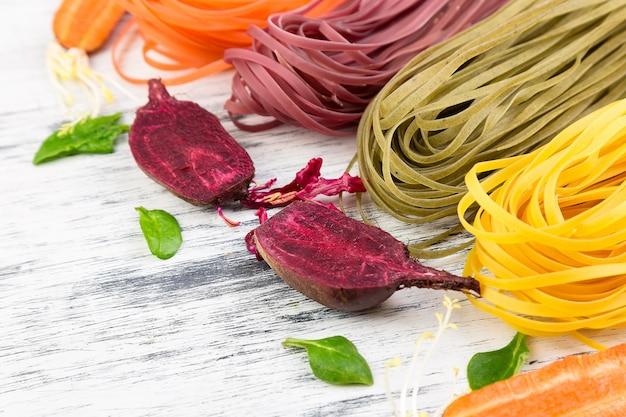 Massa colorida do vegetariano do vegetal cru com beterrabas, cenouras e espinafres.