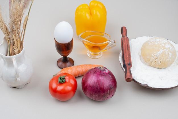 Massa com legumes e ovo na superfície branca