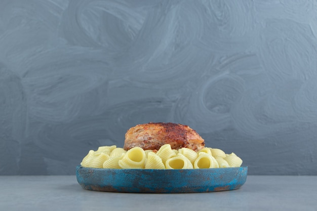 Massa conchiglie e frango grelhado na placa azul.